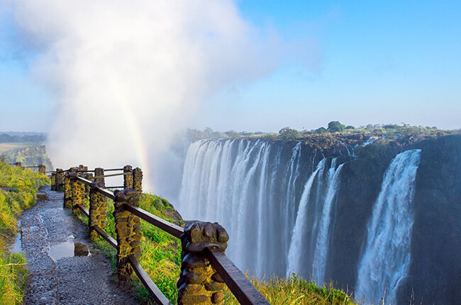 Walkway around Victoria Falls, with cascading waterfalls in background, and a small rainbow coming out of the dense mist created by the falls