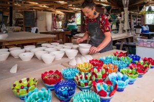 Lady making colourful craft pots in Nelson