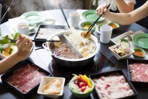 Japanese Shabu Shabu dinner with many plates and people using chopsticks