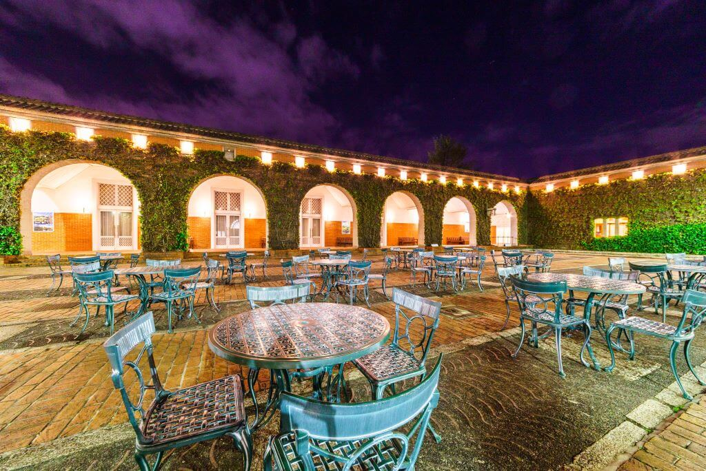tables and chairs in courtyard at night