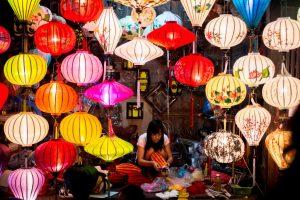 woman making lantern with many lanterns on display
