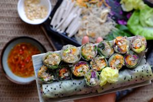 Vietnamese spring rolls on plate with ingredients in background
