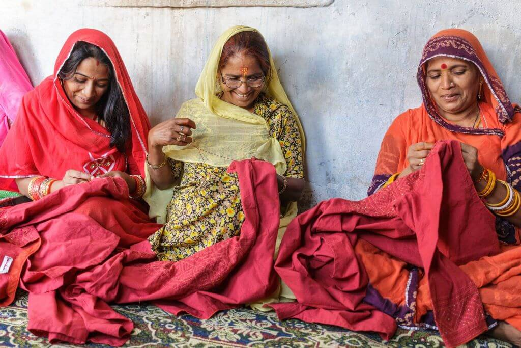 Women of Sadhna sewing and smiling