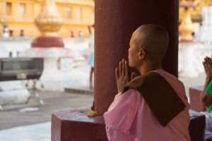 Female Buddhist praying in a temple in Kandy