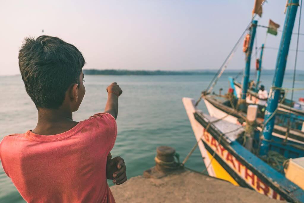 boy at harbour by fishing boat in Worli fishing village Mumbai India