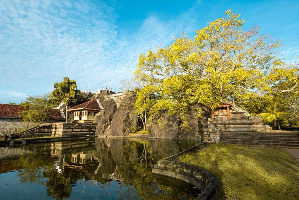Mihintale & Isurumuniya Temple outside view with tree and pond in Habarana Sri Lanka