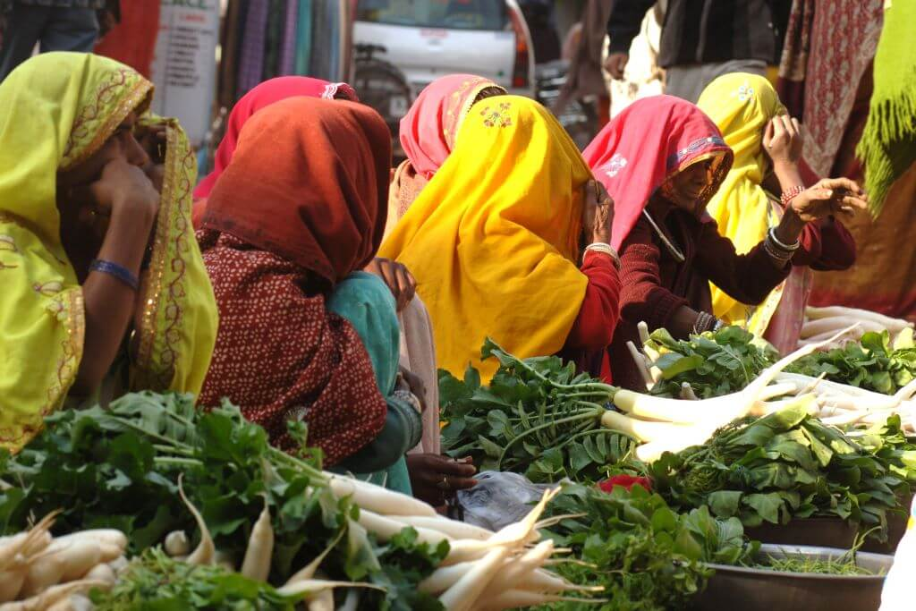 women in colourful clothes at market