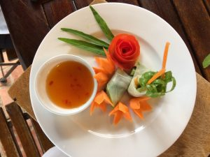 plate of vegetables crafted like flowers with pot of sauce
