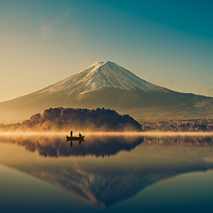 Mount Fuji at sunrise with boat on Lake Kawaguchiko
